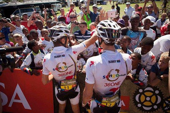 Jaroslav Kulhavy und Christoph Sauser feiern mit den Songo Kids die gewonnene Etappe - Gary Perkin-Cape Epic-SPORTZPICS