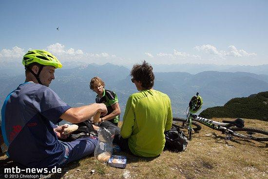 Gipfel-Snack auf dem Monte Roen. Markus Reiser (links) verteilt belegte Semmeln, Lukas und Stefan von Supertrail Map greifen gerne zu. Vor der Gruppe geht es teils fast senkrecht über blanken Fels hinunter ins fast 2.000 Höhenmeter tiefer gelegene Tal.