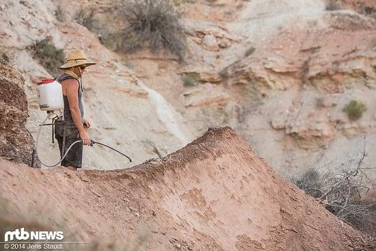 Wasser hilft beim Formen des losen Bodens und muss von den Helfern auf den Berg geschafft werden
