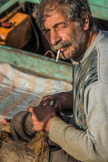 Einer der Fischer, der schon um 8 Uhr morgens einen rohen Fisch samt Gräten verputzt hat