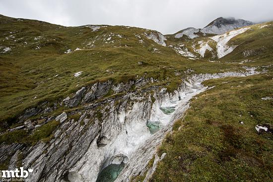 """Unscheinbarer Weg in der Karstlandschaft des Val Maliens. Die durch eine starke Strömung erzeugten Strudel erodieren den Kalkstein zum Designobjekt. """"Gletschermühlen"""" nennt sich dieses Phänomen."""