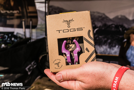 Die Togs gibt es als Kunststoff- oder Carbon-Variante. Die Carbon-Variante hat ein Schnarnier an der Unterseite zur einfacheren Montage, die Kunststoff-Variante muss über den Lenker geschoben und fixiert werden