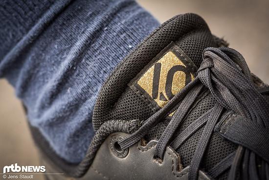 Ein goldenes Logo ziert die Zunge des Schuhs.
