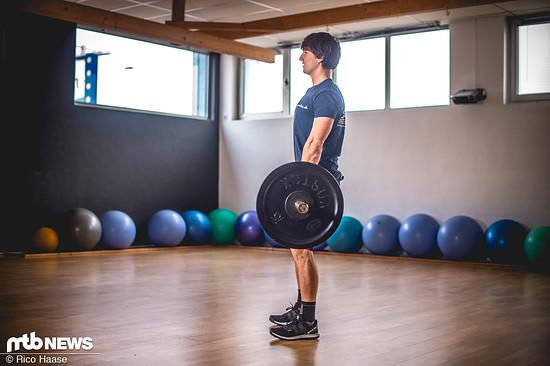 Endposition: Mit geradem Rücken stehen die Hüfte ganz nach vorne schieben. Dabei die Schultern nach hinten und die Brust herausstrecken.