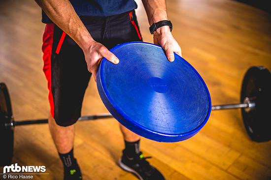 Wer der Übung etwas mehr Würze verleihen möchte, kann sich eine Balance-Scheibe dazu nehmen